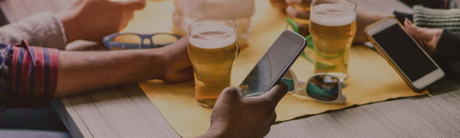 People drinking beer while checking their cellphones